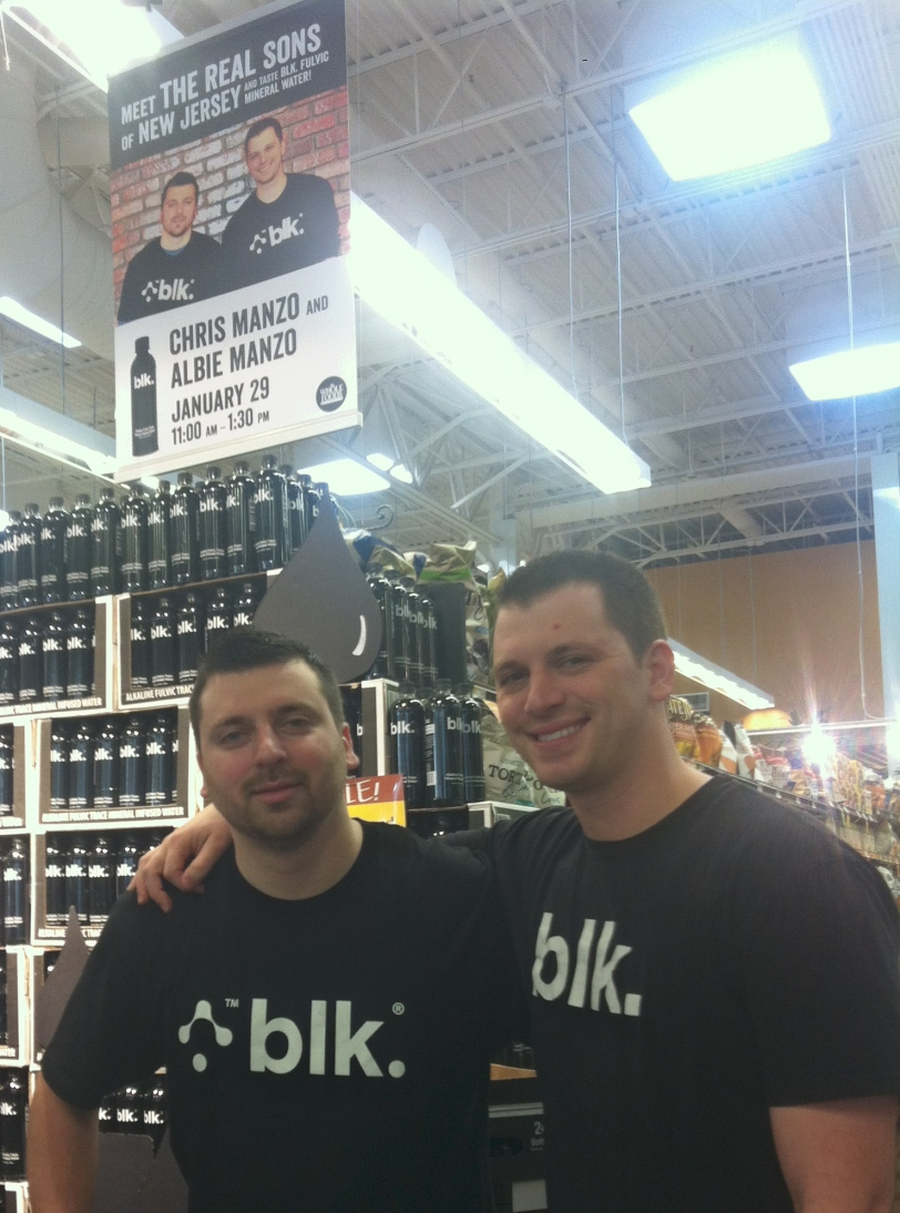 Chris and Albie Manzo in front of their blk. display at Whole Foods in Sarasota, FL.