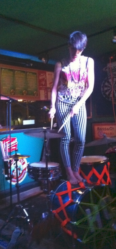 Cupcakes barefooted and playing on top of her drums.
